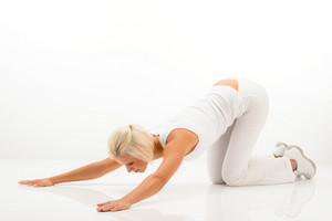 Woman stretching her back fitness yoga exercise on white floor