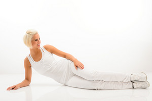 Woman stretching her body fitness exercise lying on white floor