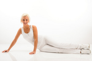 Woman stretching her body fitness exercise sitting on white floor