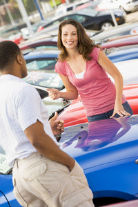 Woman talking to car salesman at lot