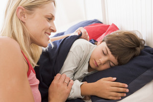 Woman waking young boy in bed smiling