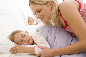 Woman waking young girl in bed smiling