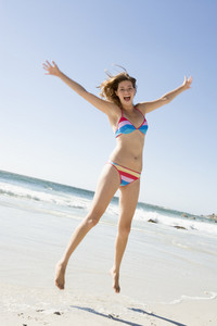 Woman wearing bikini leaping on beach