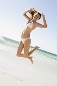 Woman wearing bikini leaping on beach