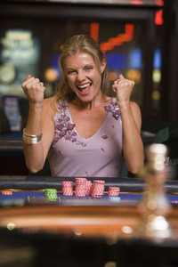 Woman winning at roulette table in casino