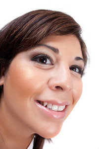 Woman with a happy look on her face smiles over a white background. Shallow depth of field.