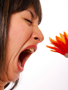 Woman With An Allergy Smelling A Flower
