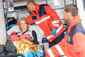 Woman with broken arm in ambulance paramedics accident helping victim