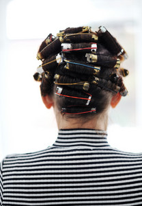 Woman with curlers on head, back