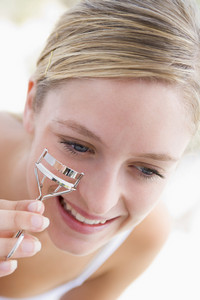 Woman with eyelash curler smiling