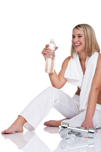 Woman with weights and bottle of water on white background