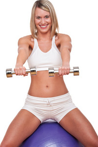 Woman with weights sitting on purple ball on white background