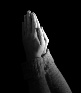 Woman's hands held up in prayer on black background.