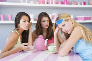 Women looking unhappy sat with friends in a cafe