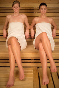 Women wrapped in towels relaxing on wooden bench in sauna