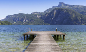 Wooden dock and a sunlit, mountainside lake