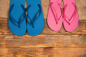 Wooden grunge background with two paar flip flop sandals