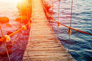 Wooden rope bridge over rocky sea coast at sunset