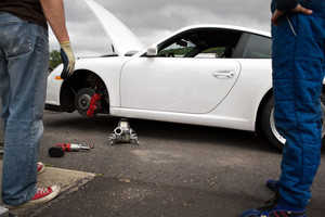 Working on the brakes and wheel assembly while in the pits at the race track.
