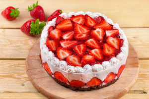 Yogurt cake with strawberries on wooden table