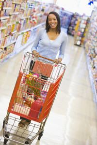 Youing woman grocery shopping in supermarket