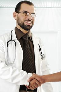 Young adult doctor shaking hand of patient and smiling