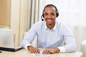 Young african american call center consultant with headset in office