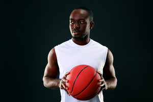 Young african american holding  basketball ball over black background