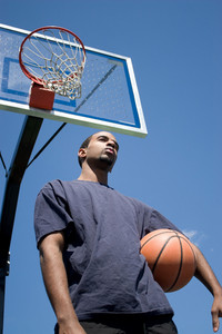 Young African American man posing with a basketball underneath the backboard.