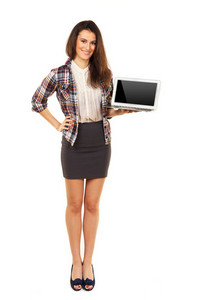 Young and attractive female holding a laptop and showing its blank screen