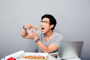 Young asian man eating pizza