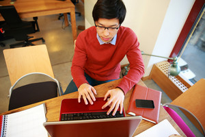 Young asian man in glasses working on laptop in office