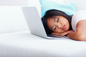 Young asian woman has fallen asleep while using laptop at home