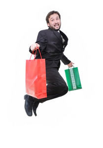 Young attractive businessman jumping with bags in hands