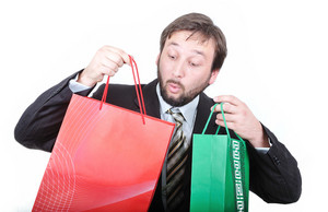 Young attractive businessman with bags in hands