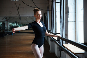 Young attractive woman practicing in ballet class