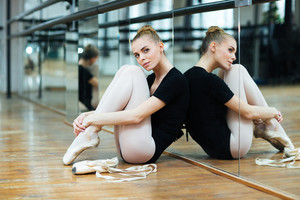 Young ballerina resting on the floor in ballet class