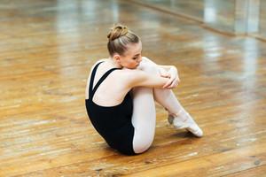 Young ballerina sitting on the wooden floor in ballet class