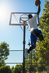 Young basketball player drives to the hoop with a high flying slam dunk. Slight lens flare.
