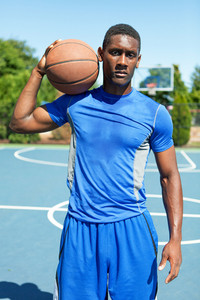 Young basketball player in his early twenties posing on an outdoor court.