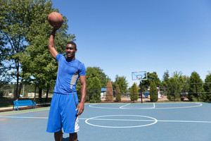 Young basketball player in his early twenties posing with the ball in one hand on an outdoor court.