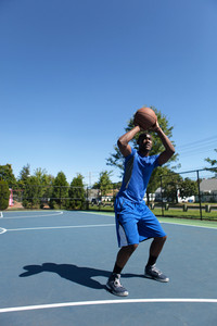 Young basketball player in his early twenties shooting the ball on an outdoor court.