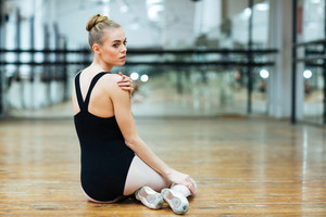 Young beautiful ballerina resting on the floor in ballet class