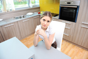 Young beautiful blonde woman in kitchen sitting on chair