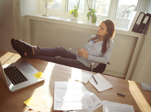 Young beautiful businesswoman at table resting with her legs on desk. Thoughtful caucasian female relaxing at her desk. Young woman taking a break from work at home office.