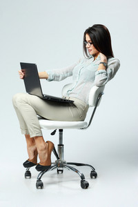 Young beautiful businesswoman sitting on the office chair and using laptop on gray background
