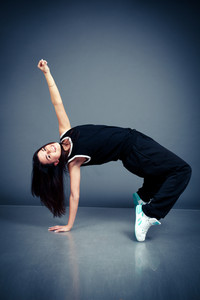 Young beautiful dancing woman in black hip-hop suit on dark background