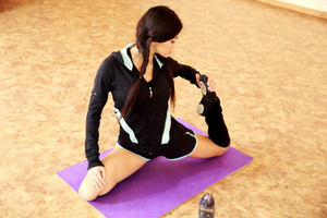 Young beautiful fit woman stretching on yoga mat at gym