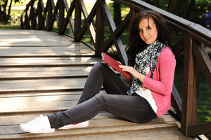 Young beautiful girl student sitting on wooden bridge in nature and reading a book