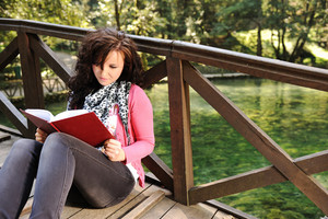 Young beautiful girl student sitting on wooden bridge over the river  in nature and reading a book